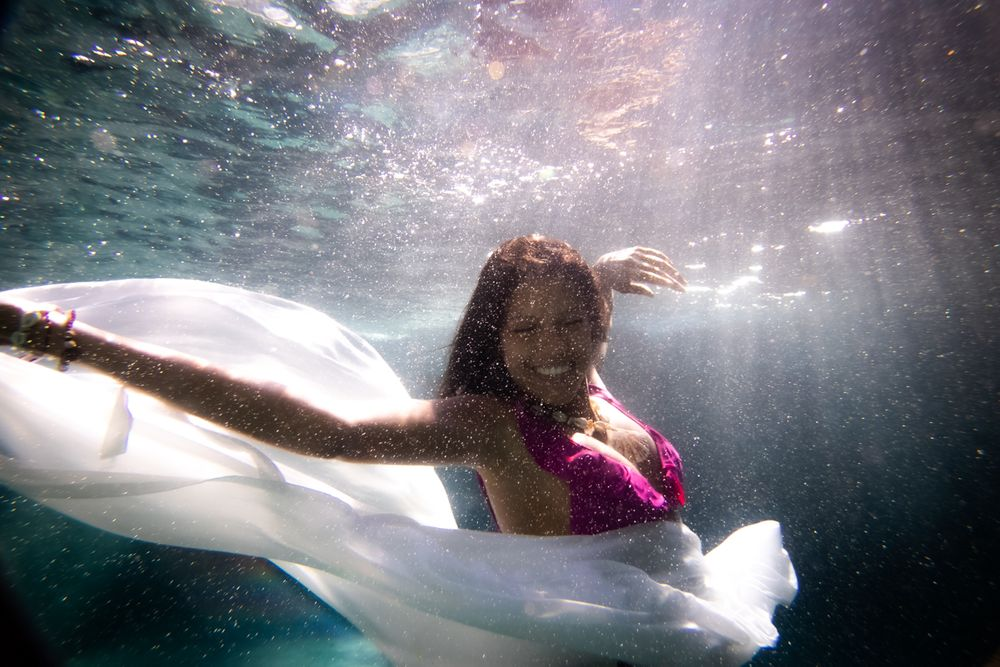 A woman smiling underwater and holding her white floating skirt
