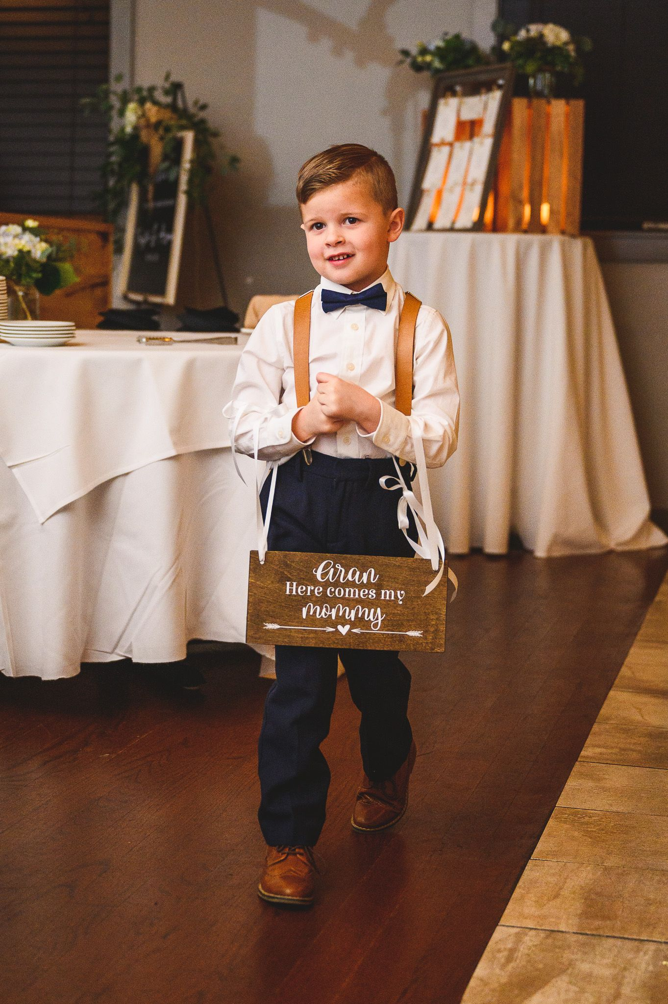 ring bearer walking down with sign during wedding ceremony