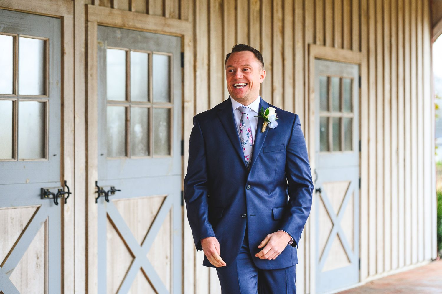 groom smiling in blue suit during the first look