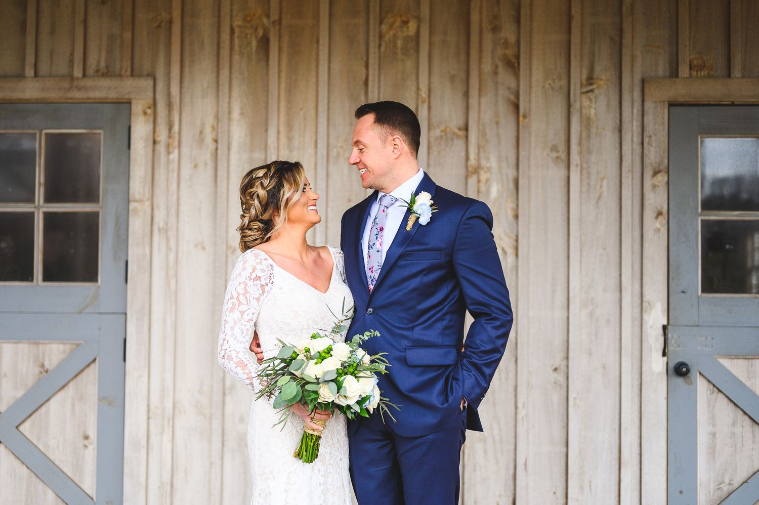bride and groom smiling at each other in front of rustic barn