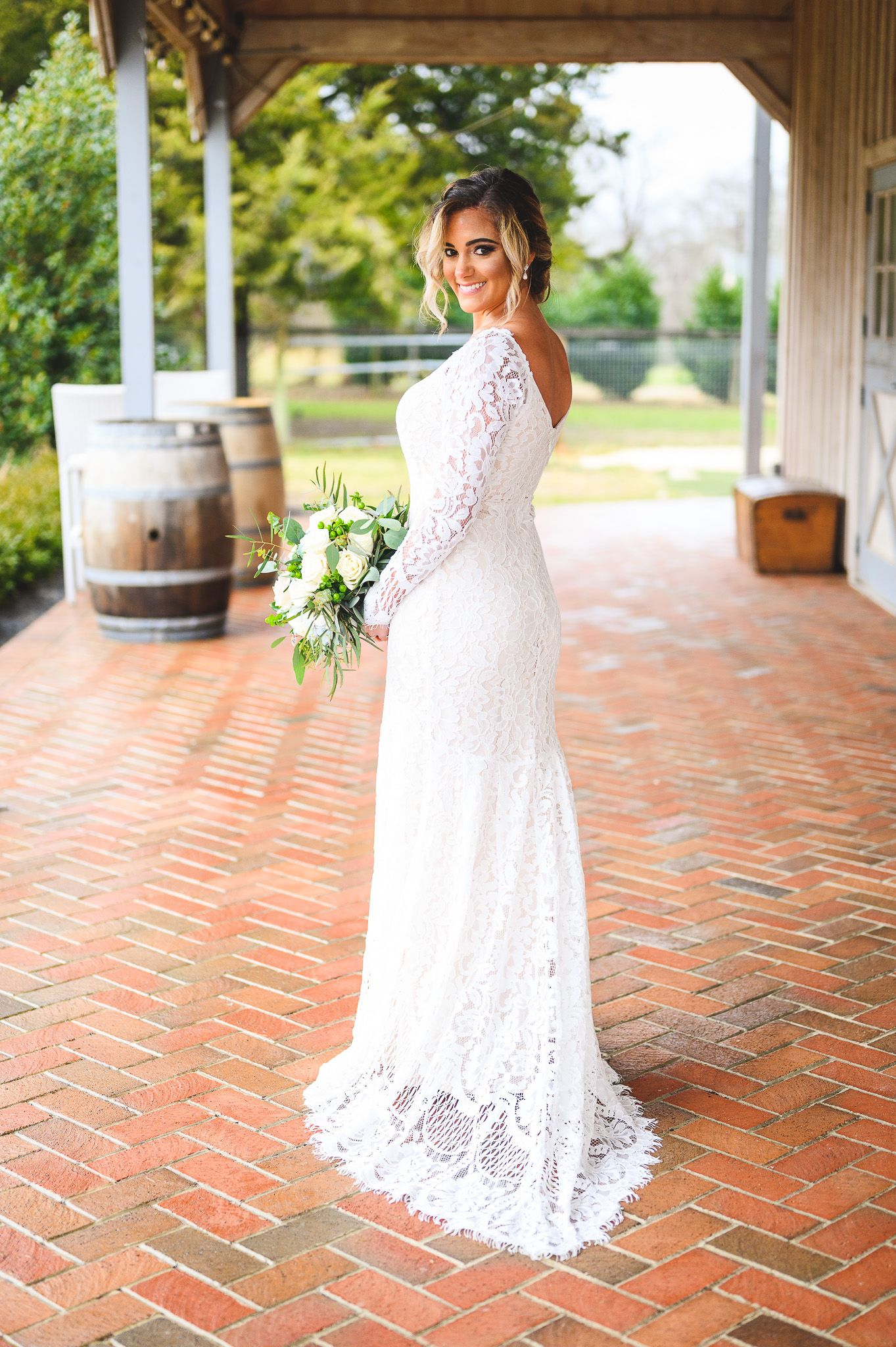 bride holding her bouquet and smiling on barnyard floor at Edel Haus alpaca farm