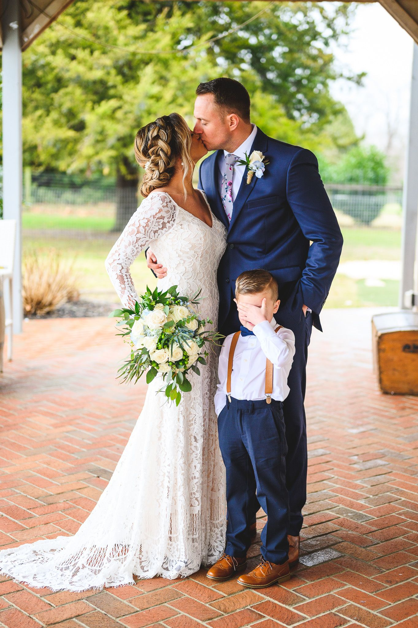 bride and groom kissing with son holding hand over face at Edel Haus alpaca farm