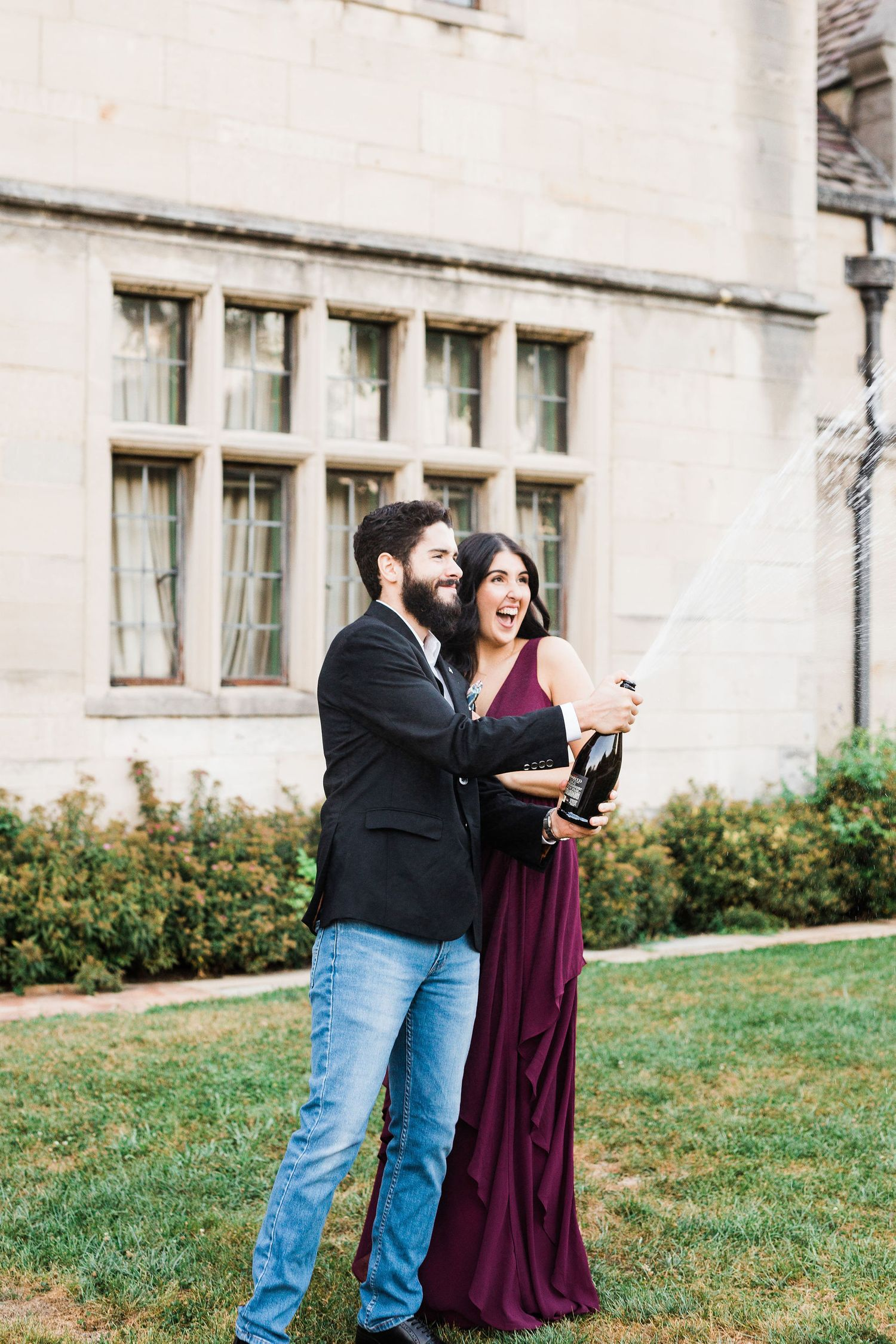 Couple popping champagne in front of Hartwood Acres Mansion