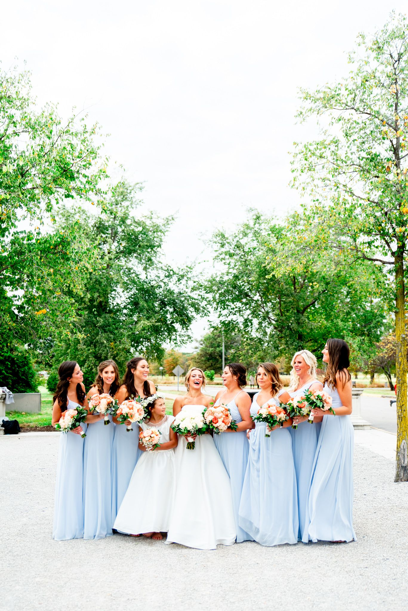 bride laughs with bridesmaids in light blue dresses and coral bouquets at STL Forest Park fall wedding\
