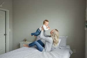 portrait of mother holding son up in air on a bed