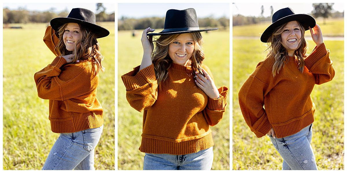 senior girl wearing burnt orange sweater and black hat standing in a grassy field