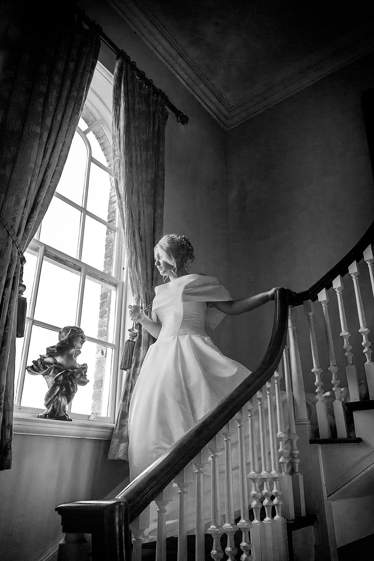 wedding photograph bride walking down stairs looking out of window with  doing in her hand at Stanbrook abbey