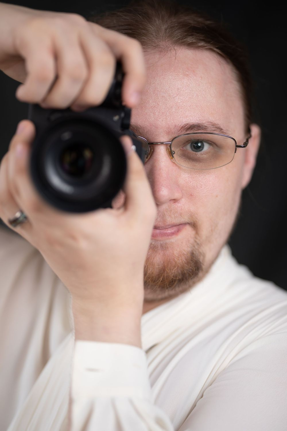 A photographer with the camera up to their eye wearing a white blouse. They have long blonde hair and a goatee