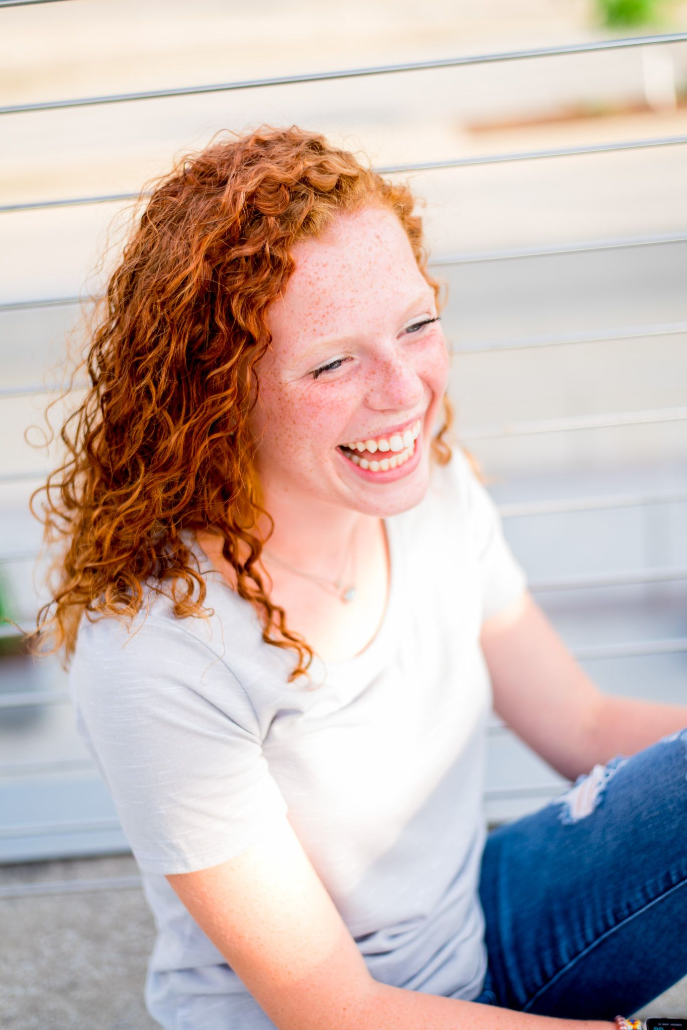 redhead girl in grey shirt laughing next to wire fence in Smale Park