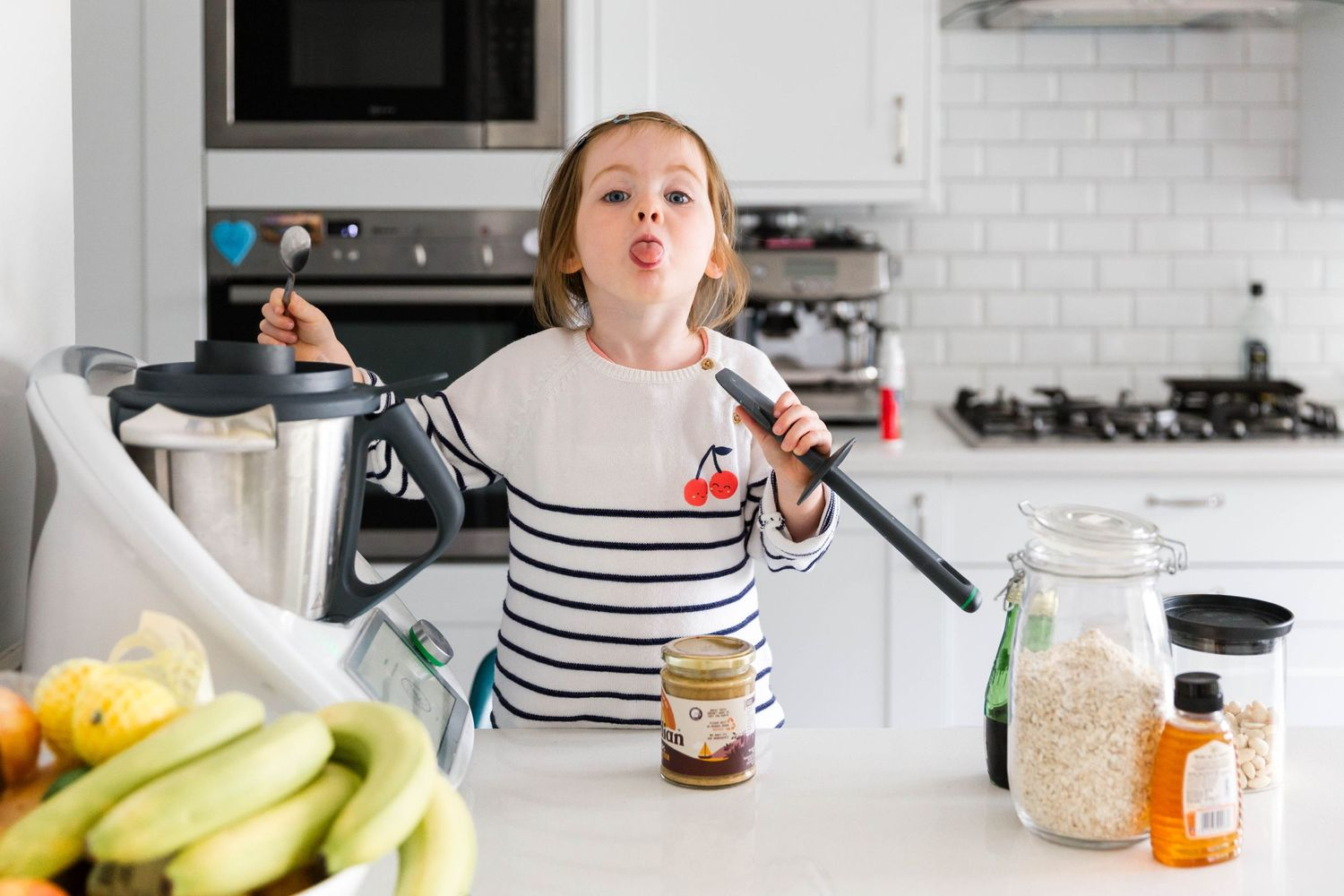little girl showing off tongue to camera cooking with thermomix tm6