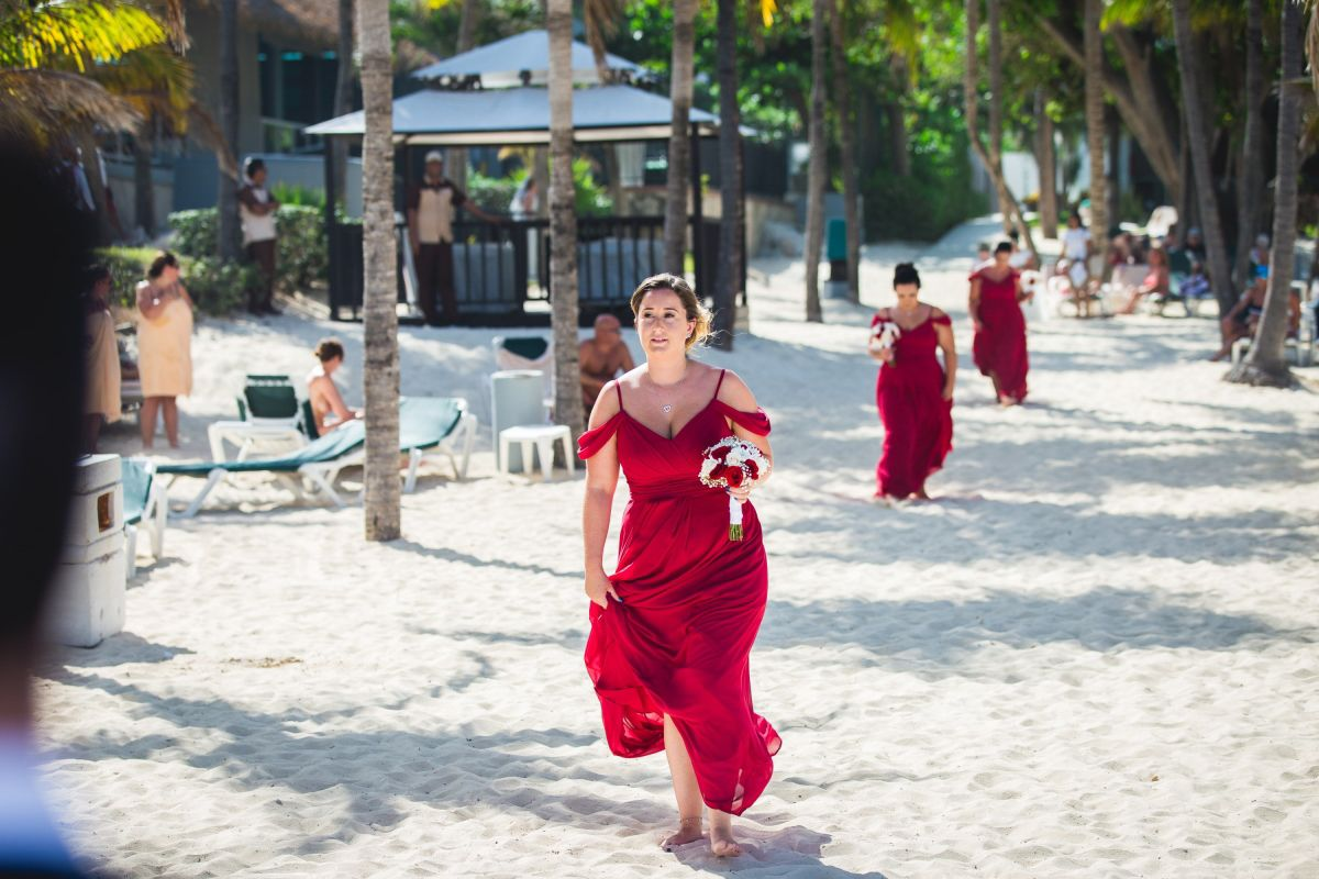 bridesmaid walking down beach to ceremony in cancun