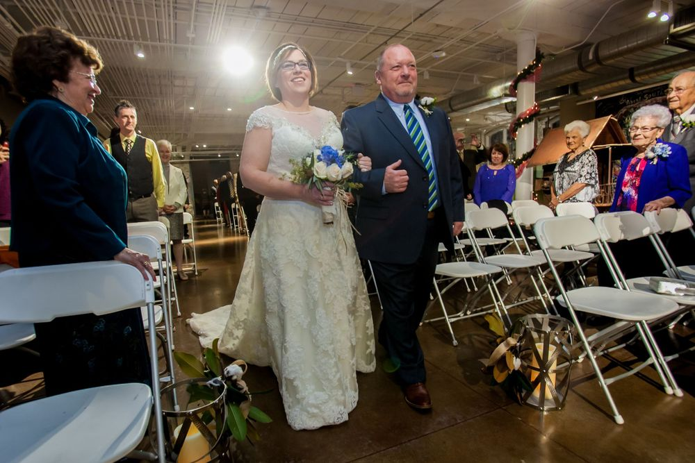 Bride Brooke is walked down the aisle by her father during her wedding at the South Carolina State Museum in Columbia SC