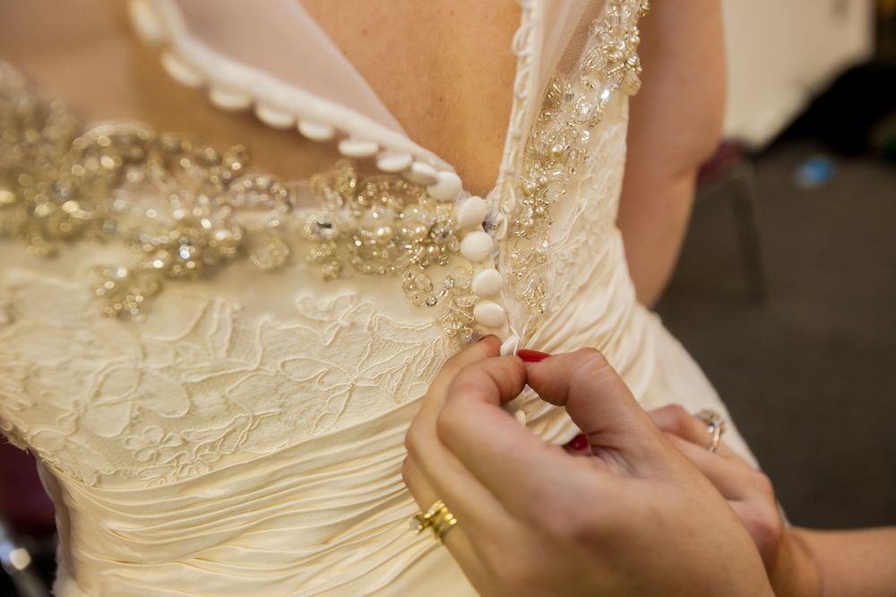 Bride Brooke's mom buttons her bridal gown before her wedding at the South Carolina State Museum in Columbia, SC