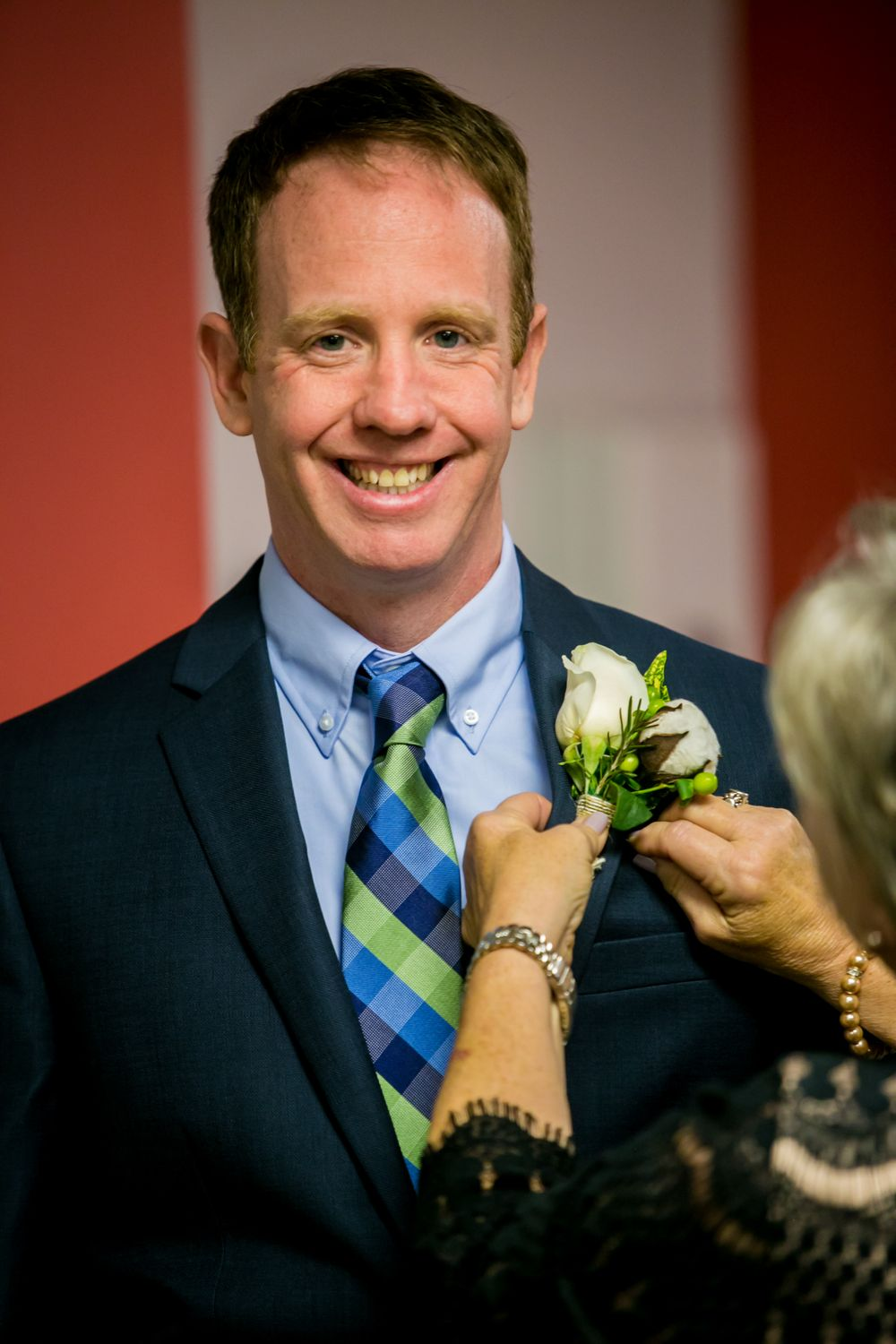Groom Jason has his boutonnière put on before his wedding at the South Carolina State Museum in Columbia, SC