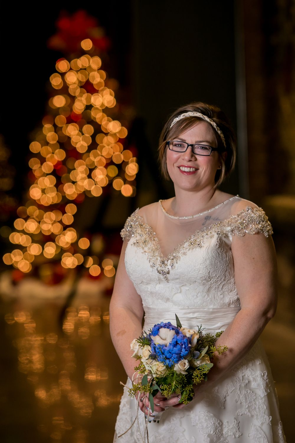 Bride Brooke poses in front of a Christmas tree before her wedding at the South Carolina State Museum in Columbia, SC