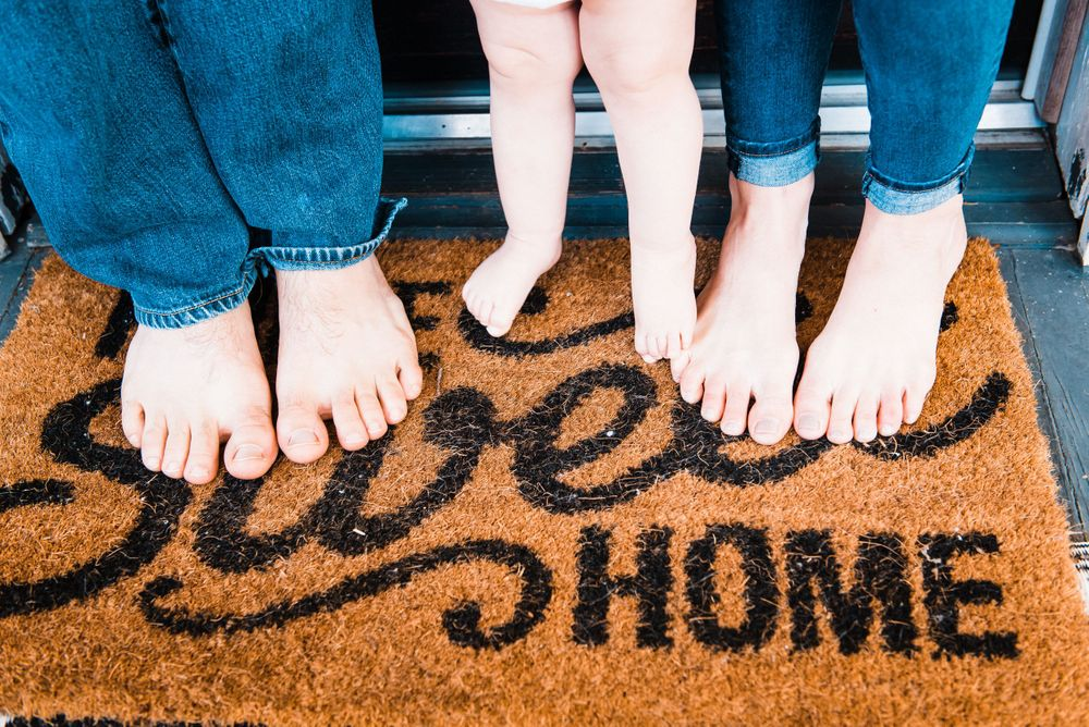 "Three sets of bare feet. Mom, Dad, and Baby stand on door mat that reads, ""Home, Sweet, Home"""