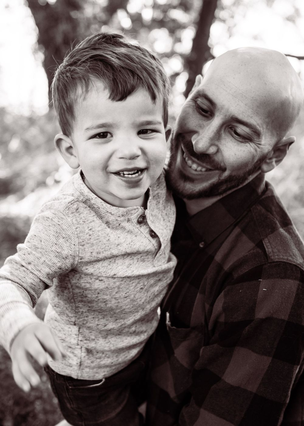 Both Dad and toddler son laugh has son reaches from Dad's arms to grab camera. Black and white photo.