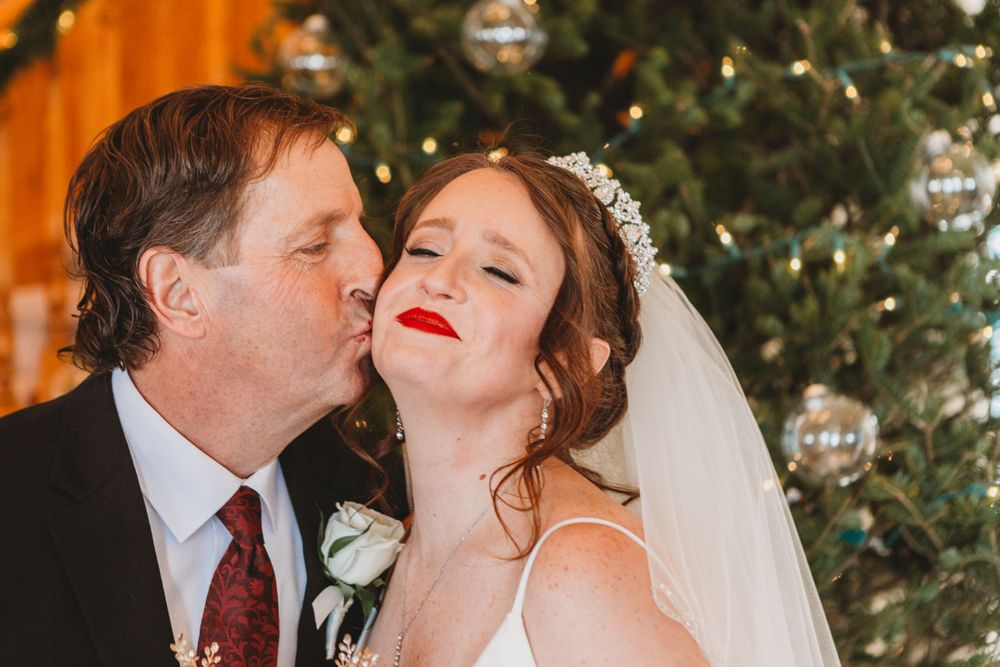 Father of the bride kisses her on the cheek during her Loveland Colorado Wedding.