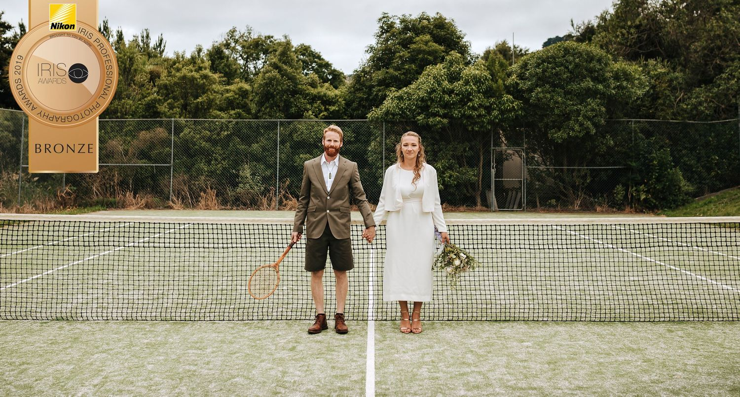 Bride and groom standing in front of net holding hands on tennis court