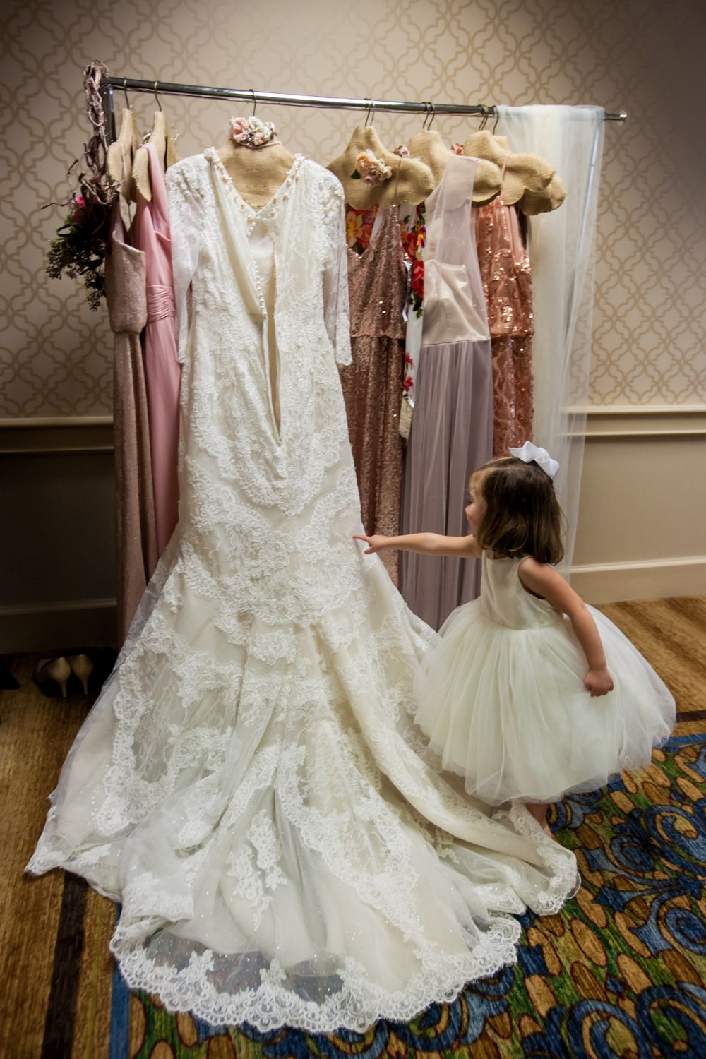The flower girl examines the bride's wedding dress while they get ready at Francis Marion Hotel in Charleston, SC