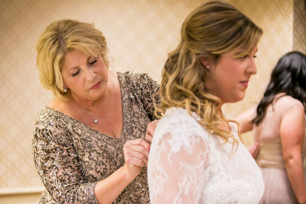 Mother of the bride helps Alissa button up her wedding dress while getting ready at Francis Marion Hotel in Charleston