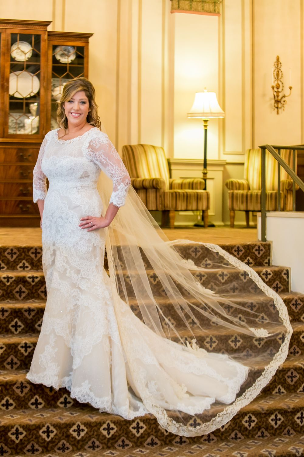 Bride Alissa poses on steps inside Francis Marion Hotel in Charleston, SC, before her wedding
