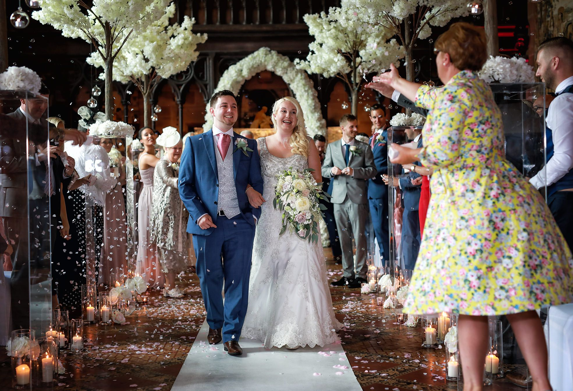 Smiling bride and groom recieve confetti as they walk up the aisle at Peckforton Castle