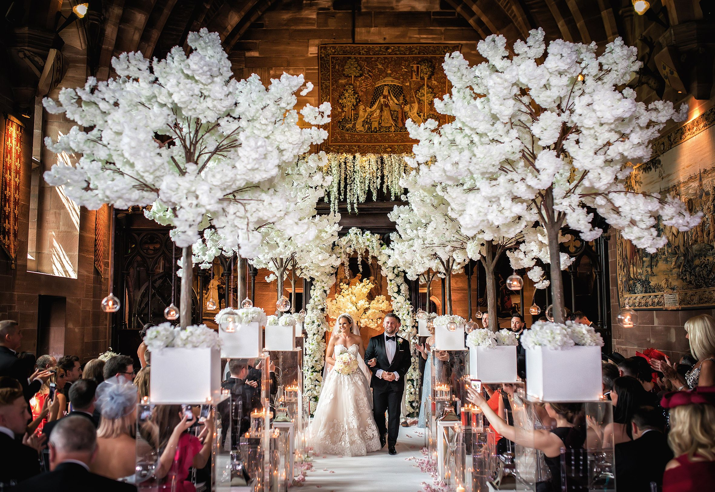 Newly wedded couple in the great hall at Peckforton Castle walk up the aisle surrounded by guests and white blossom tree