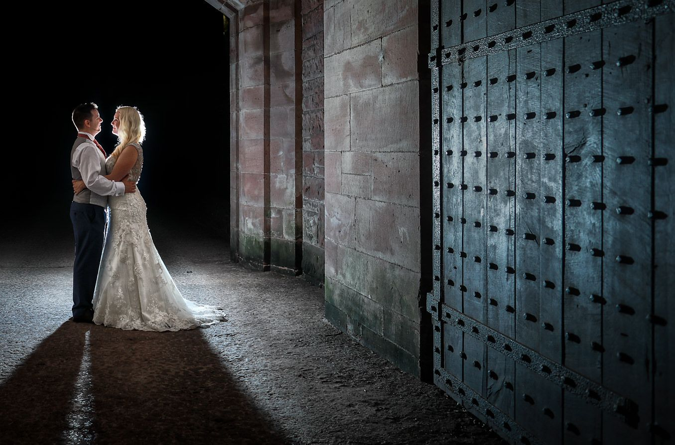 Bride and groom stand close together at night on their wedding day by a large gate at Peckforton Castle in Cheshire