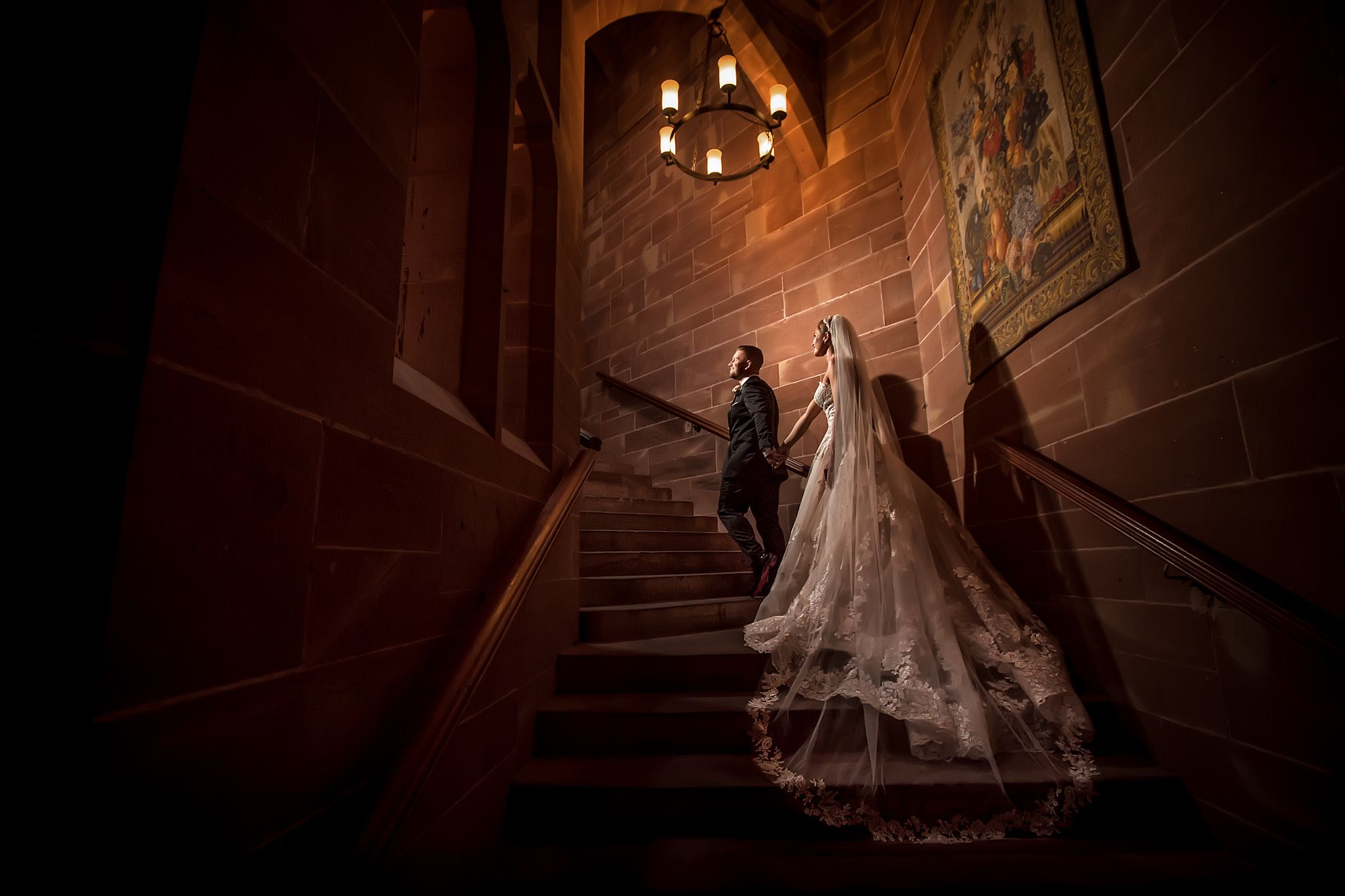 Groom leads his bride up the stone staircase on their Peckforton Castle wedding day