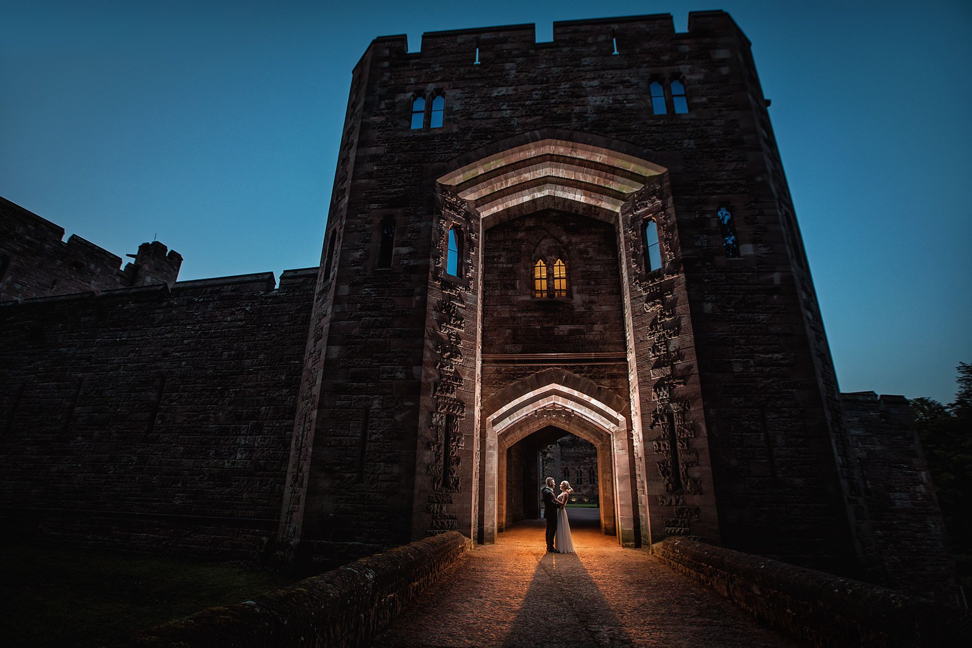 Night time at the entrance to Peckforton Castle showing bride and groom hugging each other