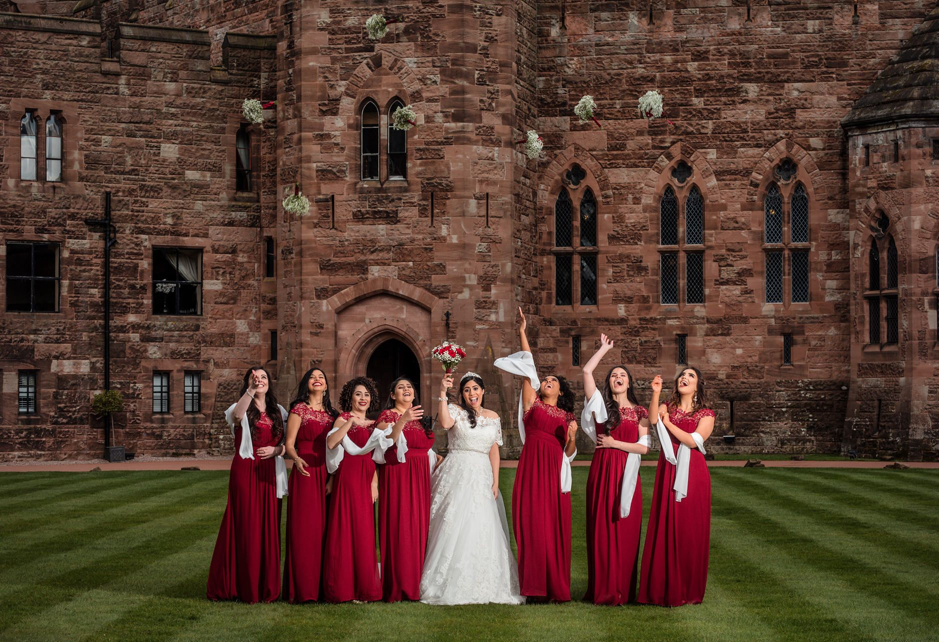 Bridesmaids wearing red dresses and bride in white throw their bouquets on the grass lawn of Peckforton Castle