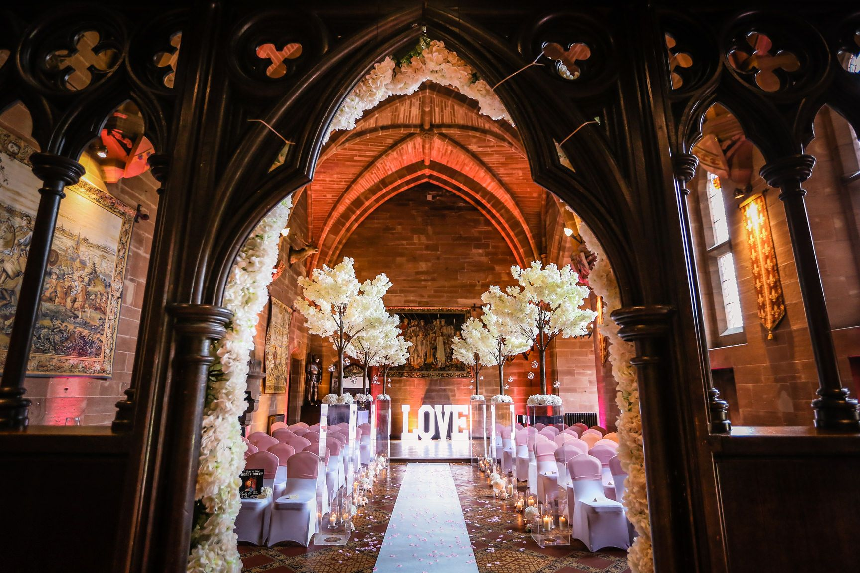Wedding ceremony interior flower decorations at Peckforton Castle in the great hall
