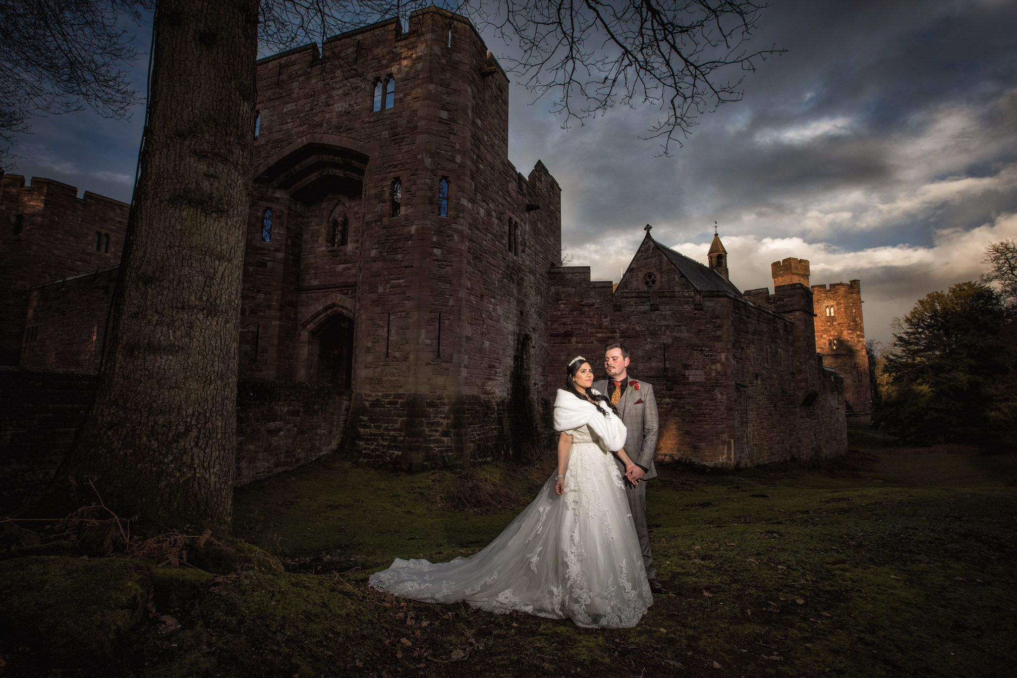 Groom admires his bride outside the walls of Peckforton Castle against a dramatic sky