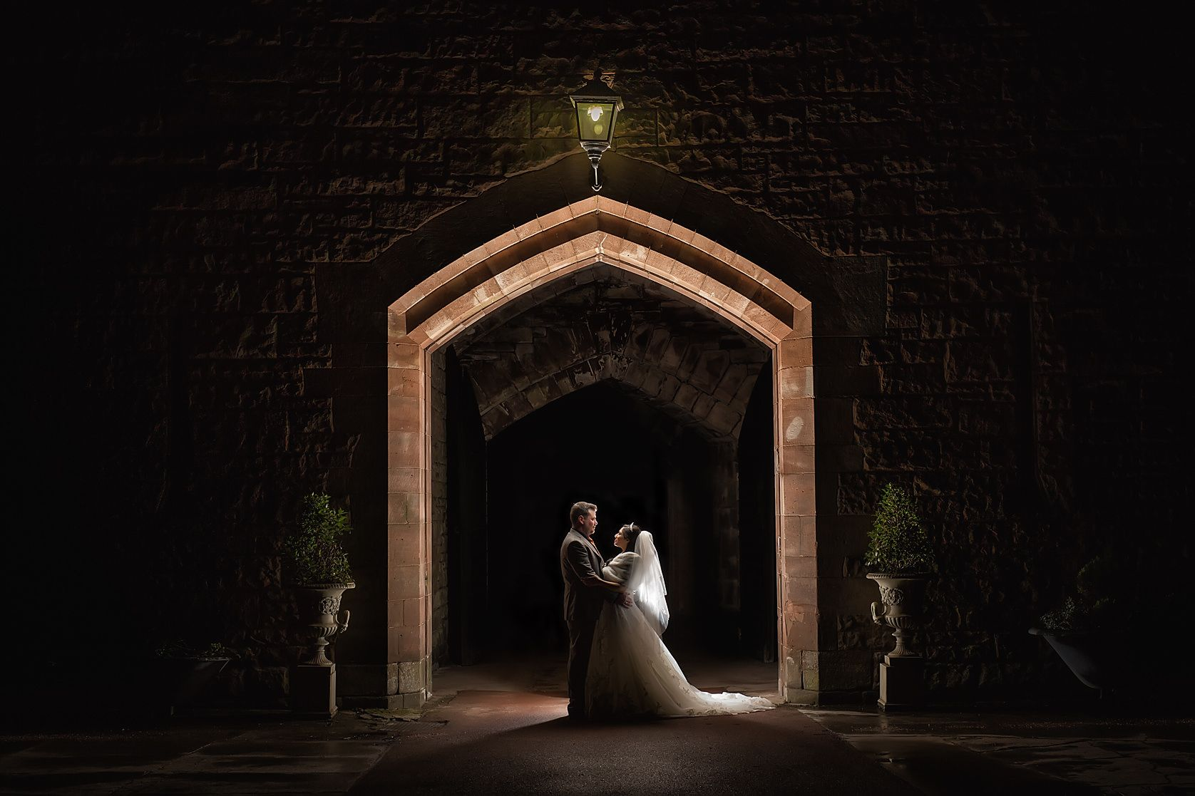 Newly married couple embrace beneath the arched gate way of Peckforton Castle at night