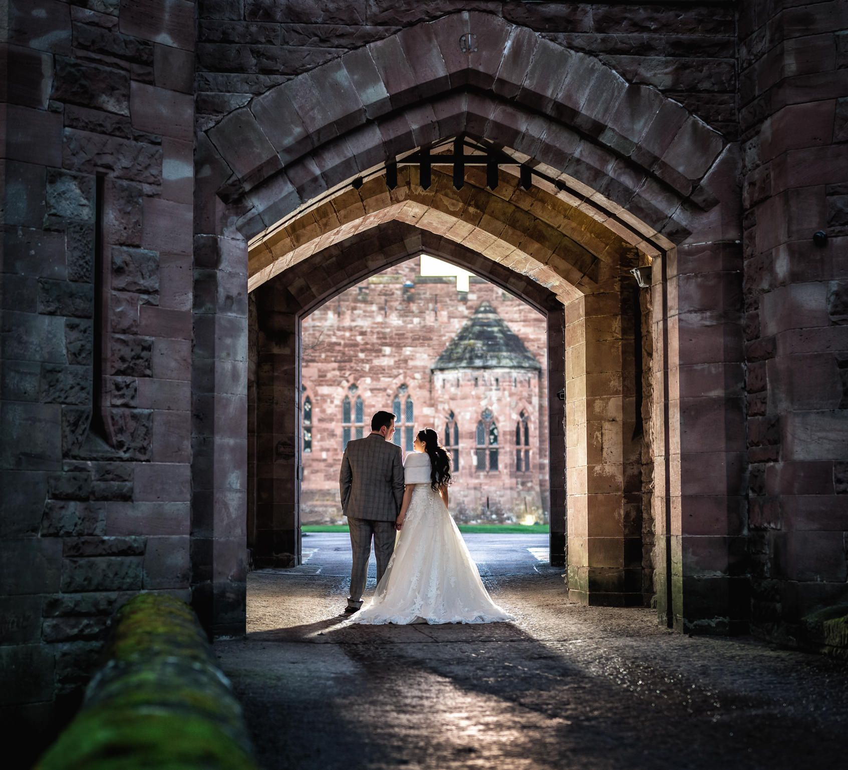 Bride and groom walk back to Peckforton Castle through the portcullis gate