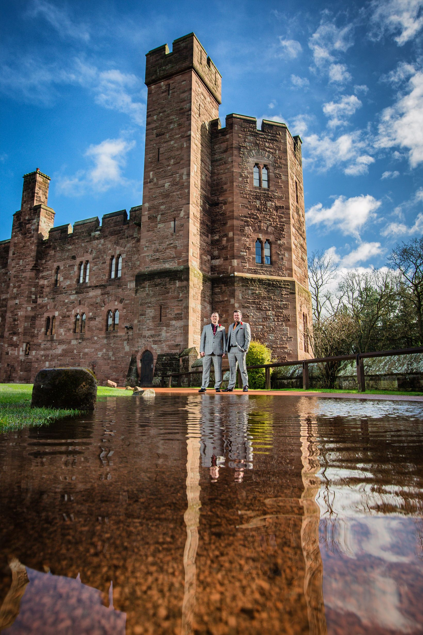 Groom and best man stand reflected in a large rain puddle outside Peckforton Castle in Summer