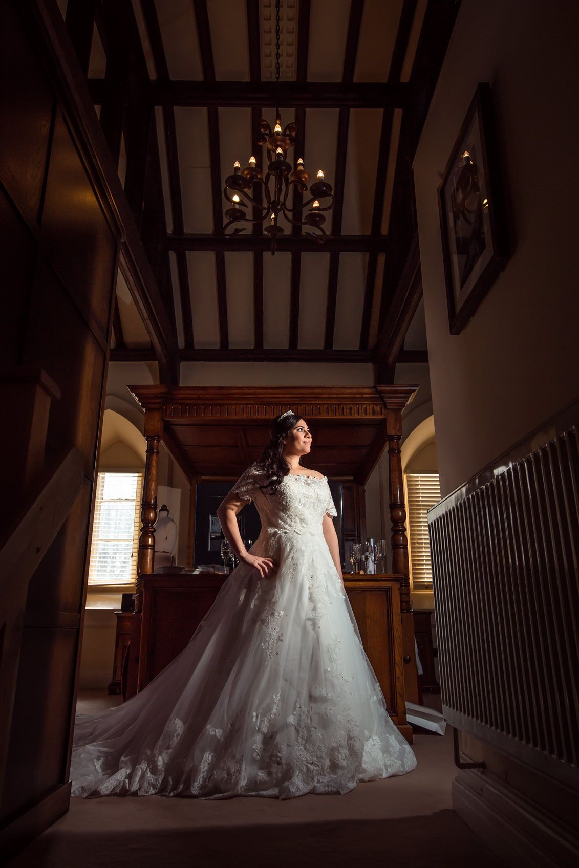 Bride stands and poses in her white wedding dress in the bedroom at Peckforton Castle