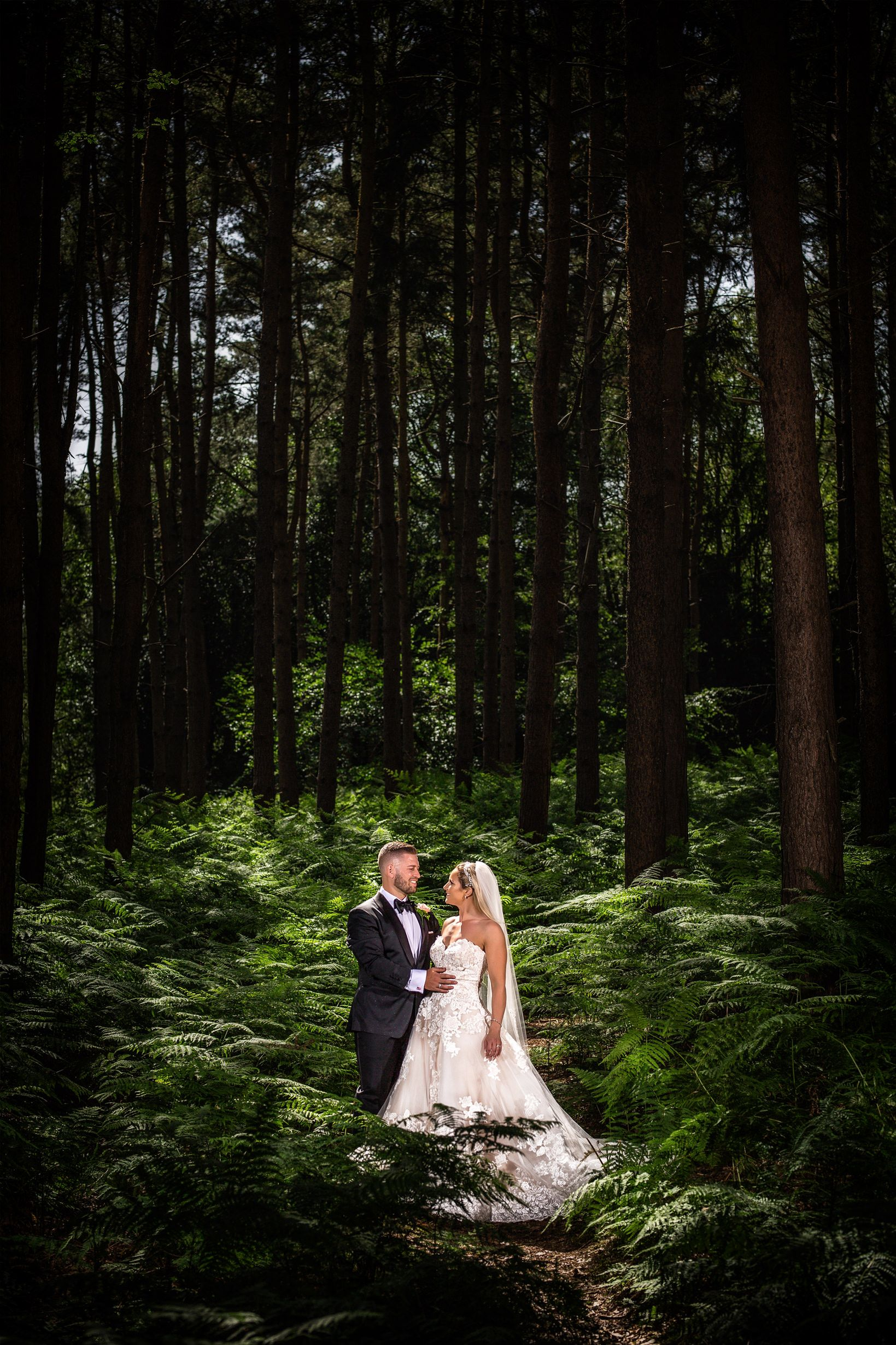 Suited groom and bride in white dress stand together amongst the tall trees at Peckforton Castle forest