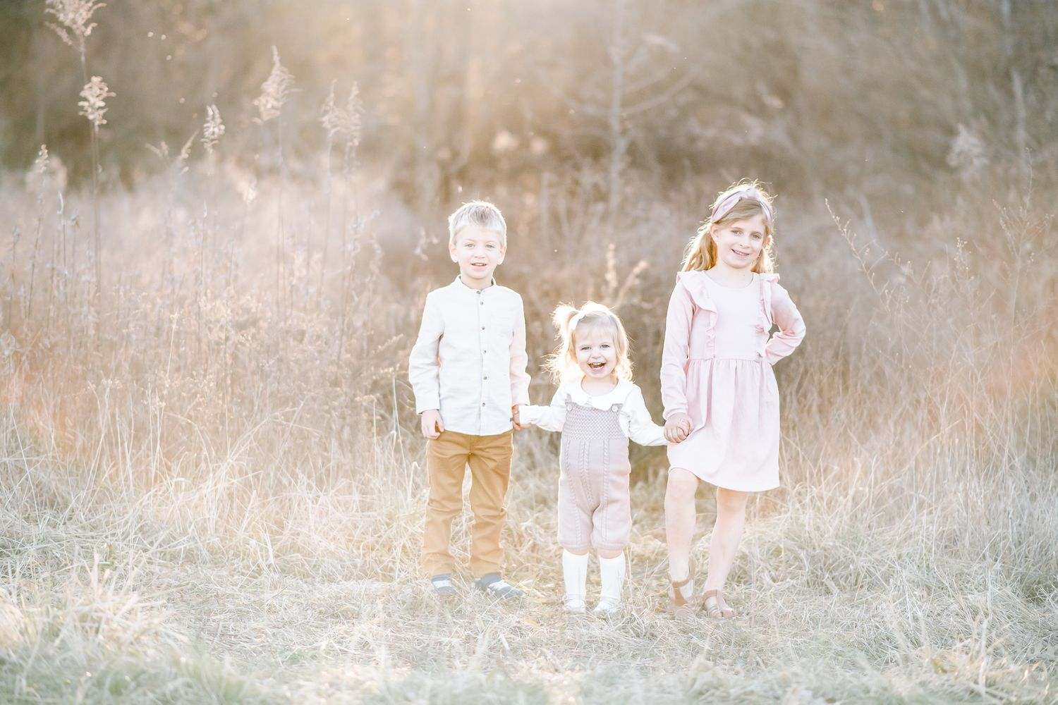 Three siblings hold hands in a field with sun flare around them