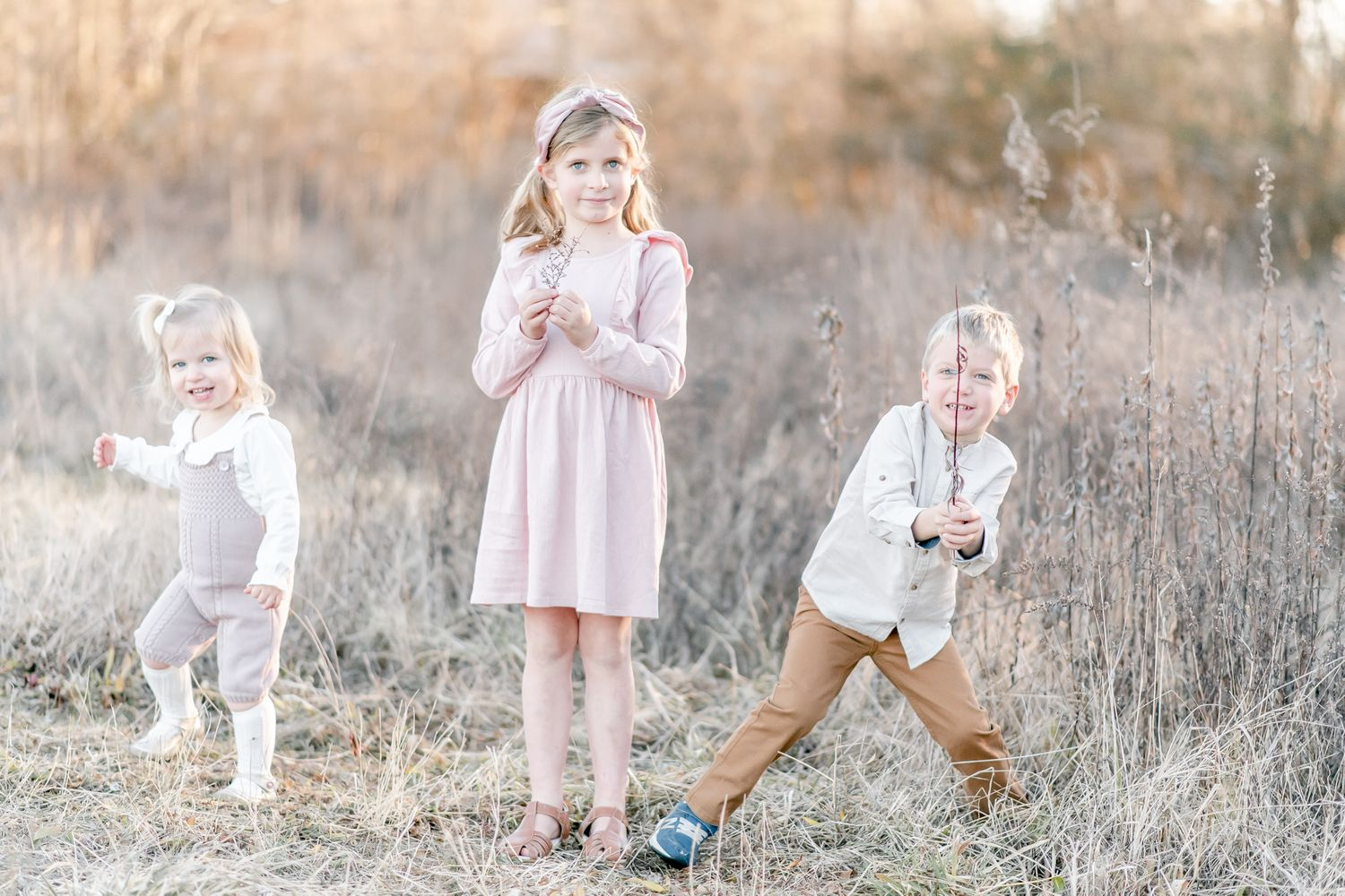 Siblings play in a field at sunset