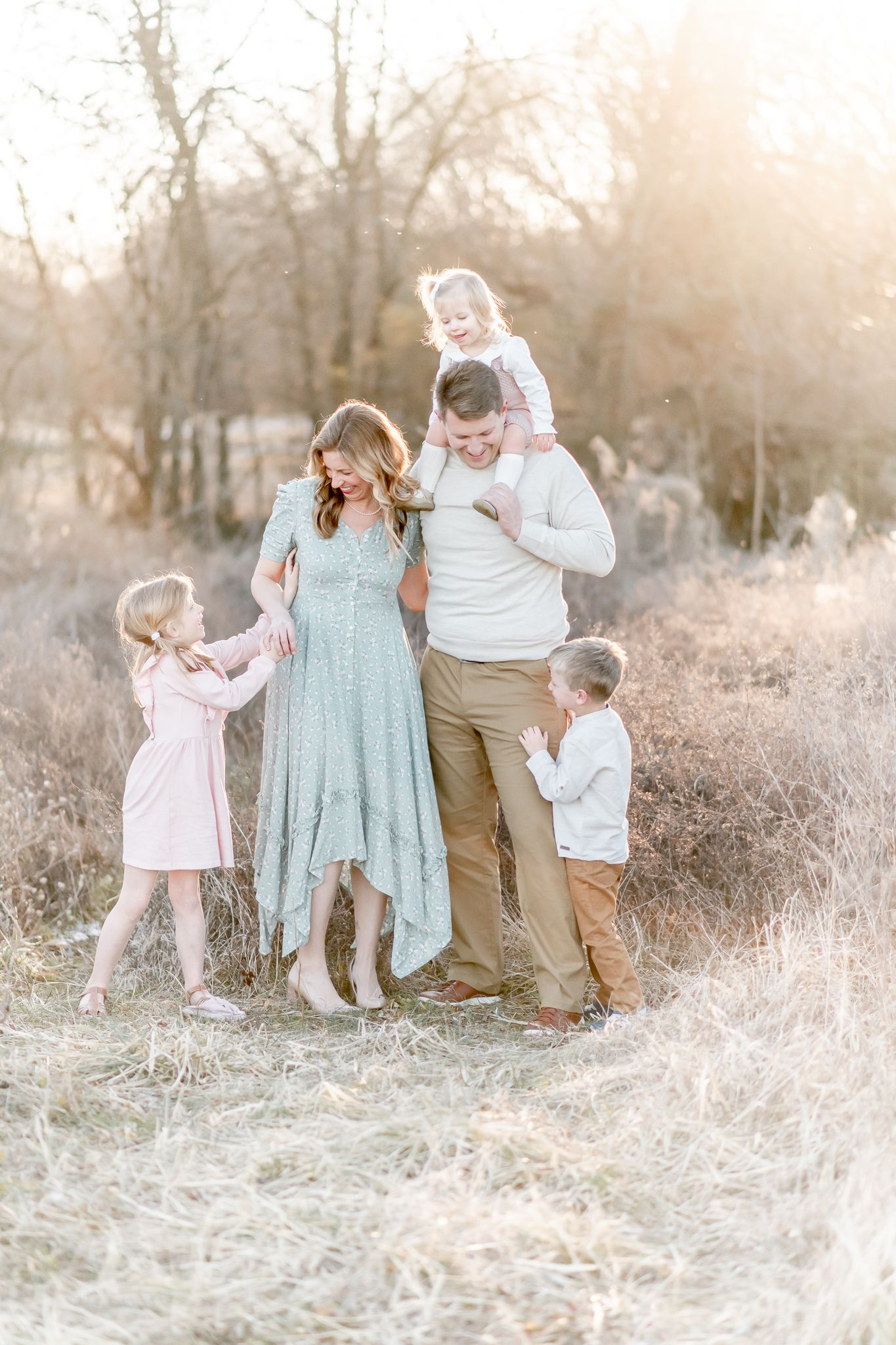 Family of 5 pose in a field with toddler on dad's shoulders