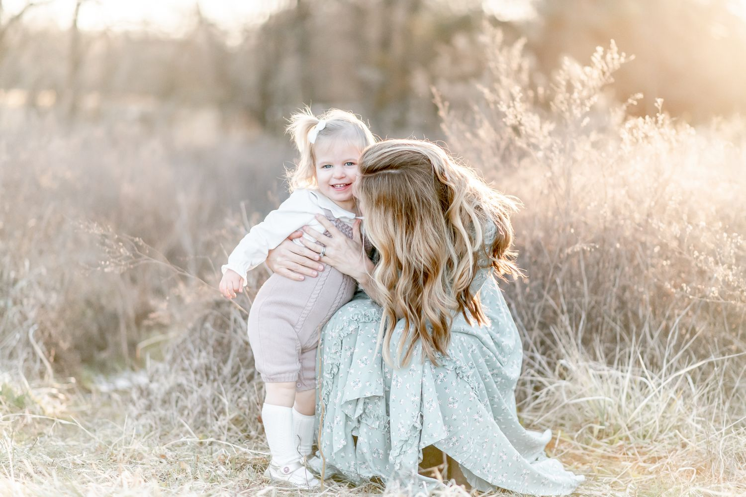 Mom snuggles with toddler girl in a field at sunset