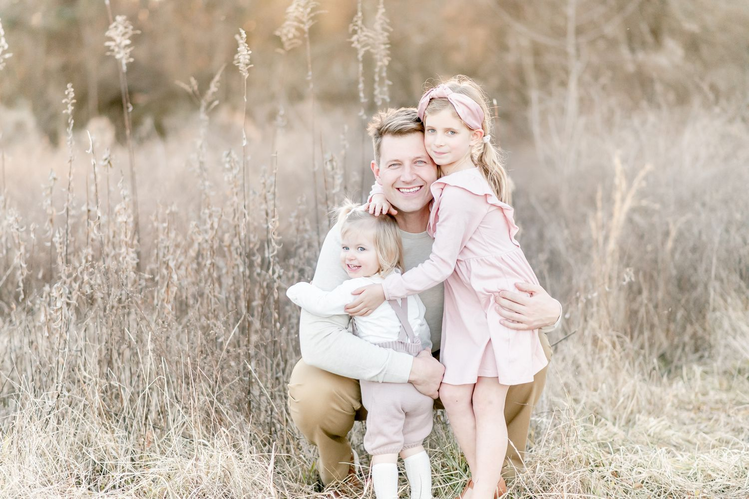 Father snuggles with his two daughters in a golden field