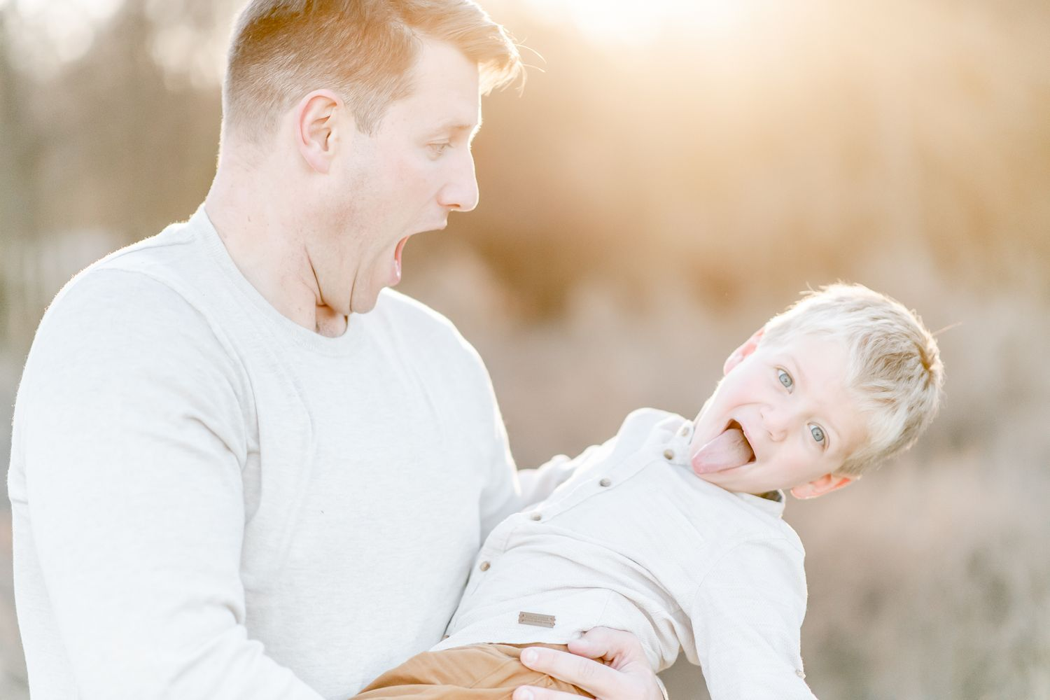 Father holds son as he leans back and sticks out his tongue