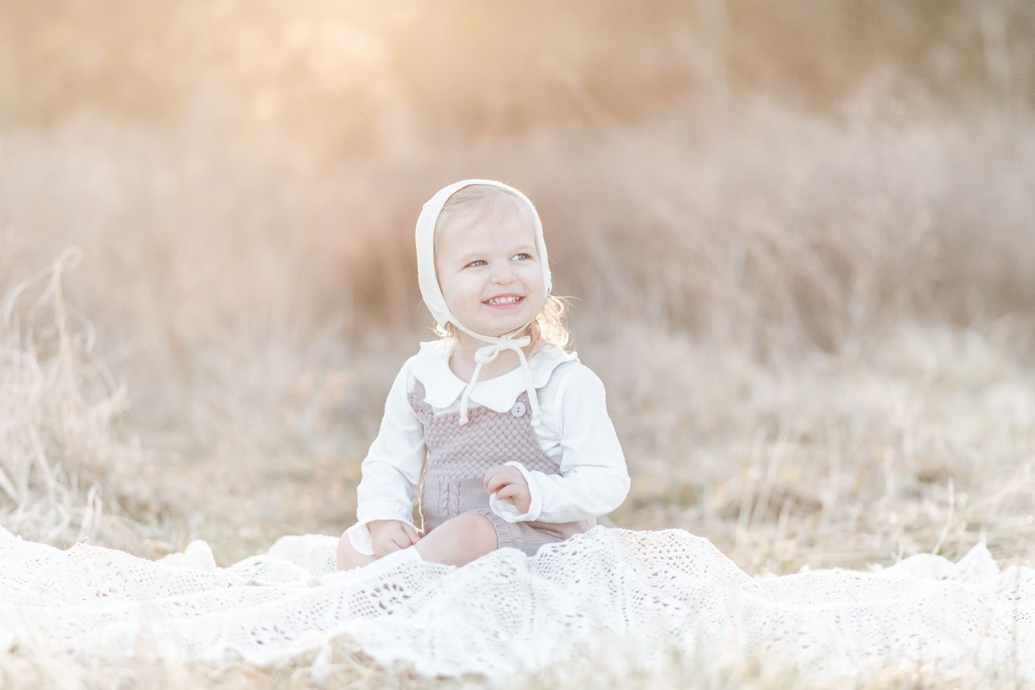 Baby girl in a white Briar Baby Bonnet sits on a blanket in a field at sunset