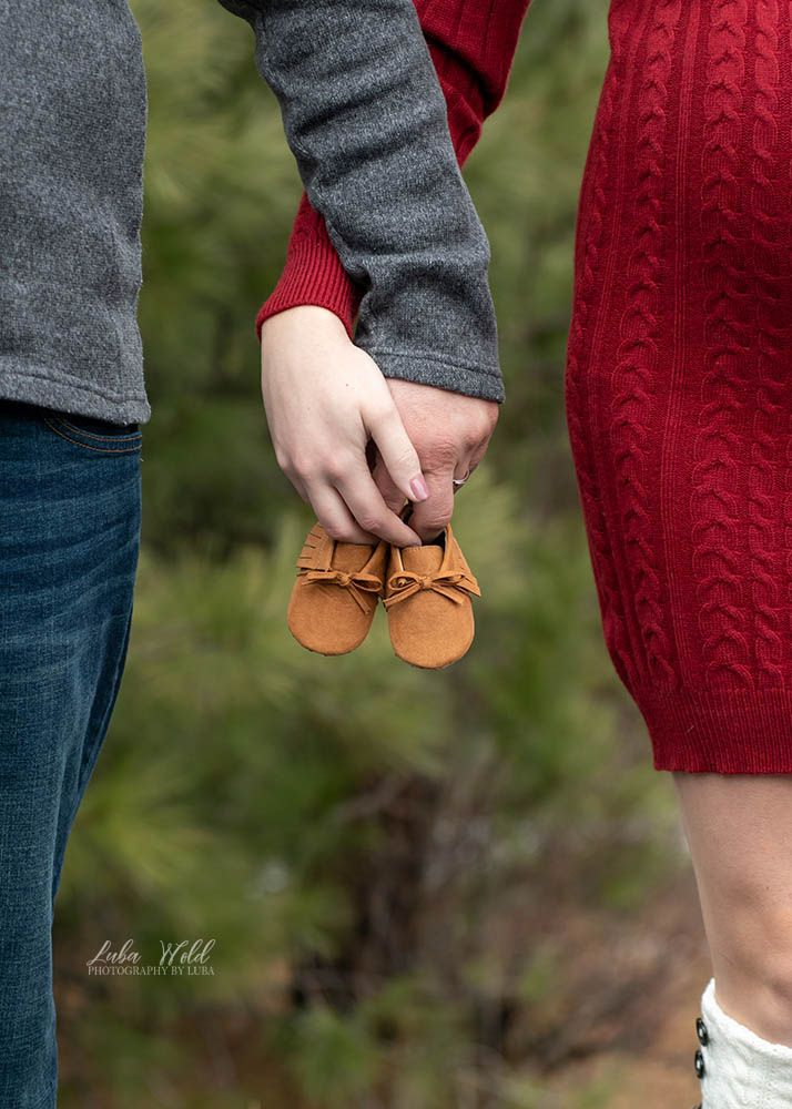 expecting a baby maternity parents hands holding baby shoes red and grey photographer luba wold spokane Coeur d alene