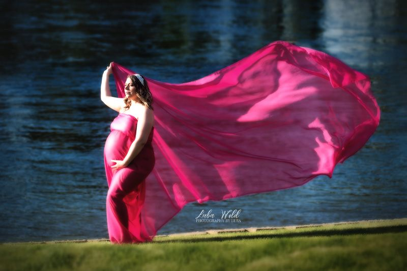maternity pregnant woman in pink flowing fabric by spokane river in coeur d alene Idaho photographer luba wold