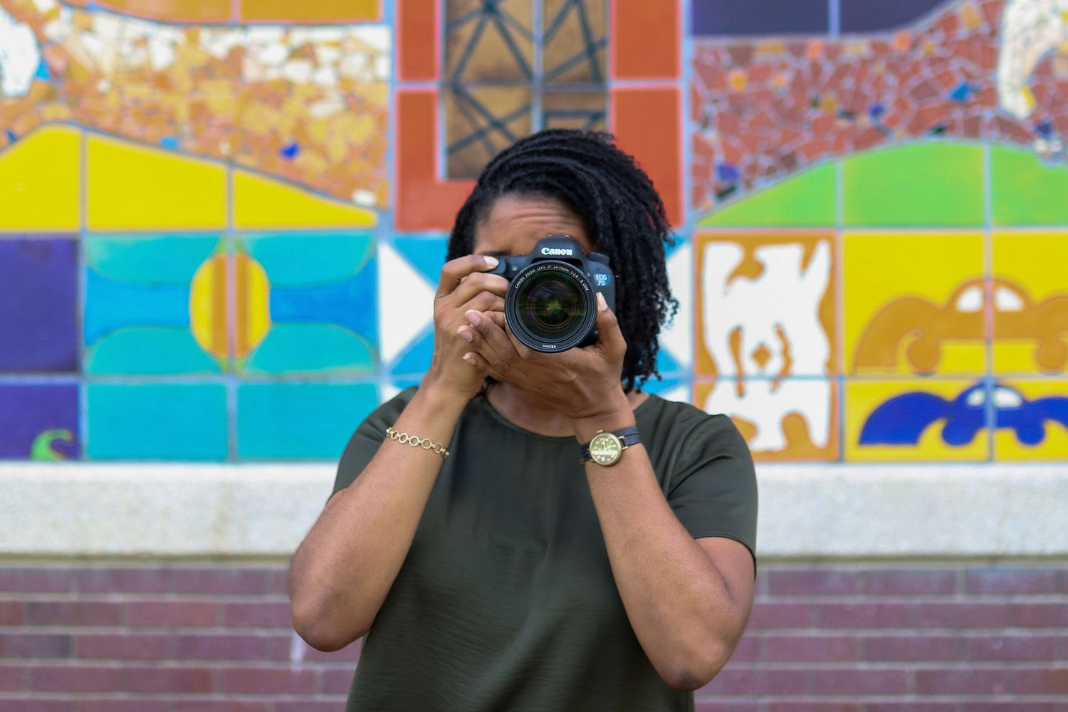 Image of RED by Morgan owner and photographer in front of a colorful mural holding a camera preparing to shoot head-on.