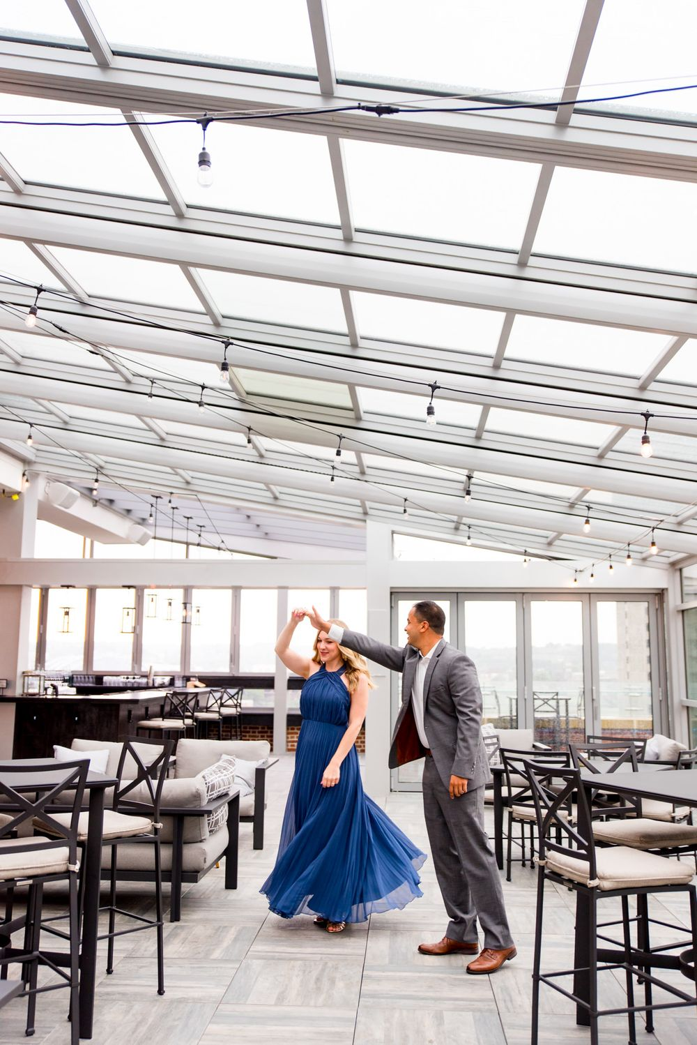 man in grey suit twirling woman in long blue dress on Lytle Park Hotel rooftop engagement pictures